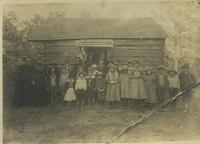 Photograph of Martha Berry with students in front of the Original Cabin, Mount...