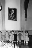 Photograph of Clara Ford and female students standing underneath a portrait...
